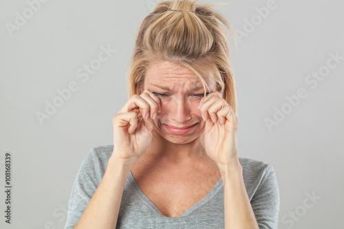Fotografía  Concepto de teatro - triste mujer joven rubia llorando con grandes lágrimas confortándola descomponer y la tristeza, el estudio de fondo gris