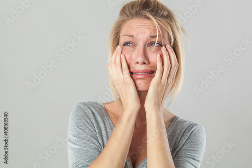 Wallpaper Mural drama concept - crying young blond woman in pain with big tears expressing her disappointment and sadness, grey background studio