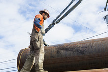 Caucasian Worker Hauling Pipe At Construction Site