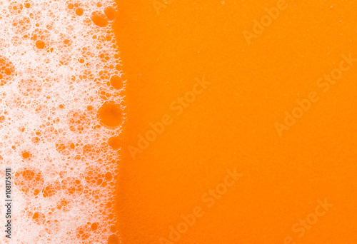 Valokuva  foam on orange background macro