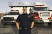 Caucasian Firefighter Smiling Near Fire Trucks