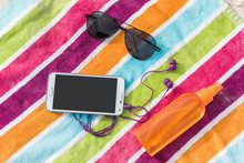 Summer Vacation Beach Accessories - Smartphone, Sunglasses, Sunscreen. Travel Packing Essential Must-have Items To Bring On A Holiday Trip To The Caribbean. Tech Phone With Music App And Earphones.