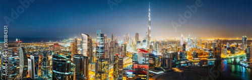 Aerial panoramic view of a big futuristic city by night. Business bay, Dubai, United Arab Emirates. Nighttime skyline.
