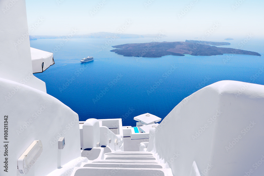 Fototapeta White wash staircases on Santorini Island, Greece. The view toward Caldera sea with cruise ship awaiting.