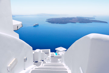 White wash staircases on Santorini Island, Greece. The view toward Caldera sea with cruise ship awaiting.