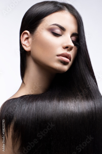 Carta da parati Beautiful brunette girl in move with a perfectly smooth hair, and classic make-up