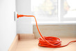 canvas print picture - Orange extension into power outlet indoors