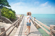 beautiful young woman running along the bridge against the back