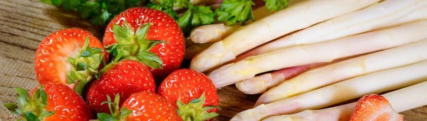 Panel Szklany Warzywa Stangenspargel mit Erdbeeren auf einem Holztisch