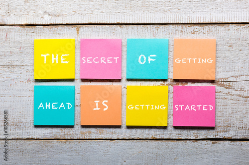 Retro white wooden table with motivational quote on colorful sticky notes