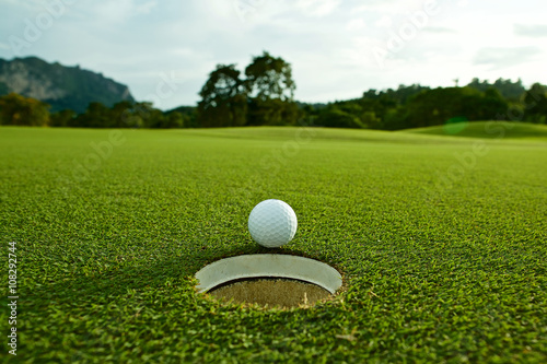Poster Golf the flare lights photo of white golf ball near hole on fairway w