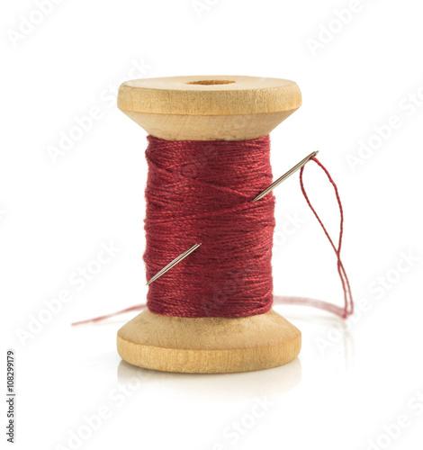 spool of thread and needle on white Fototapeta