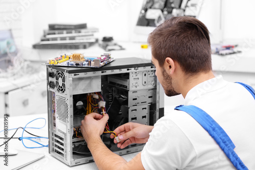 Young repairer disassembling a computer internal parts in