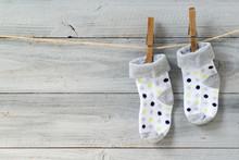 Baby Socks Hanging On Clothesline On Wooden Background