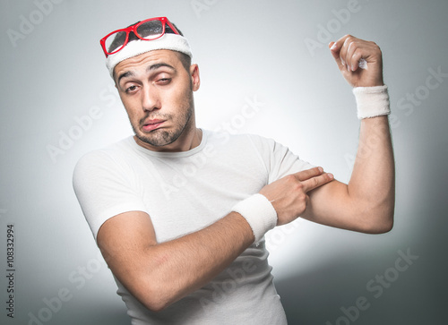 Fotografia, Obraz  Crazy man testing the flabby muscle under her arm - biceps pulling it down with her hand as she checks for muscle tone or weight gain