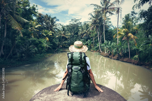 Cuadros en Lienzo Woman traveler with backpack sitting on the edge and looking at tropical river (