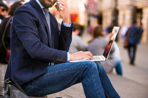 Photo  Manager with laptop and smart phone, Piccadilly Circus, London