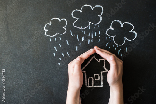 Fotografering  hands protects a house from the elements - rain or storm