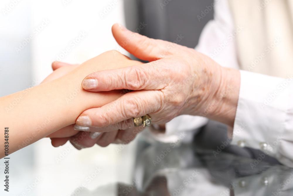 Fototapeta Pomocna dłoń. Dłoń starszej kobiety przytula dłoń dziecka