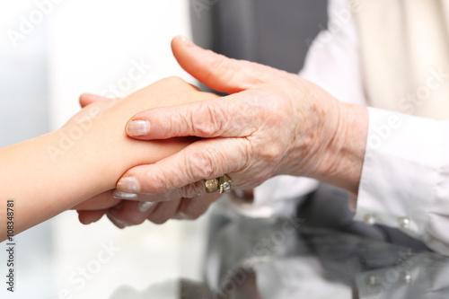 Fototapeta Pomocna dłoń. Dłoń starszej kobiety przytula dłoń dziecka  obraz