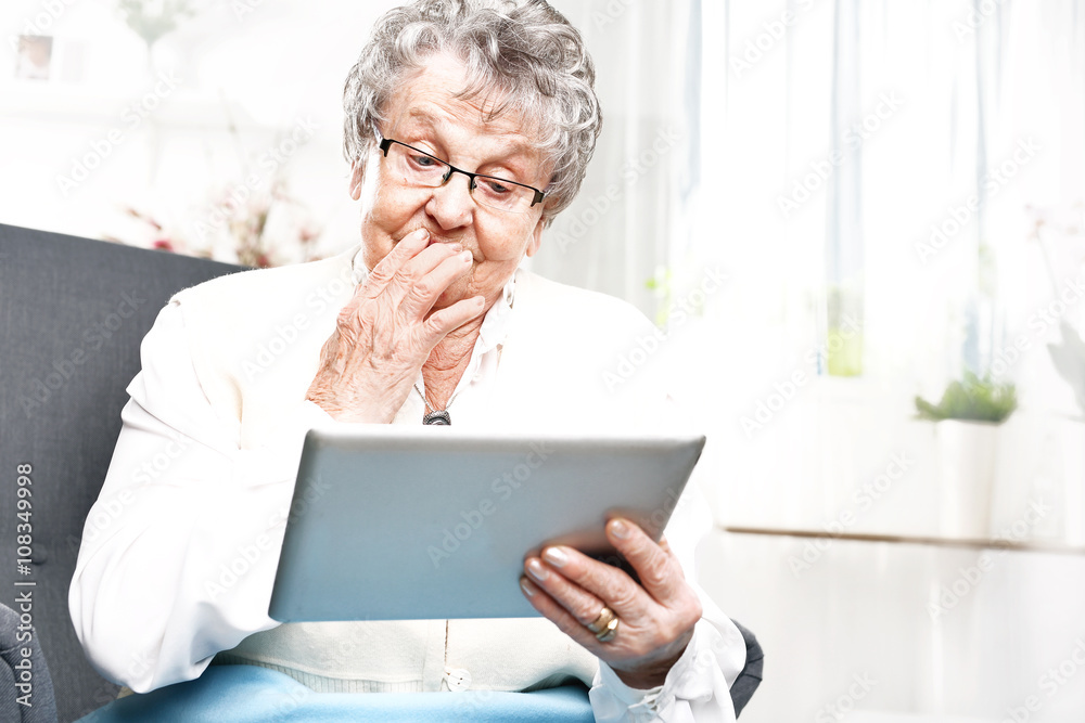 Fototapeta Na emeryturze, rozrywka w internecie. Starsza kobieta serfuje po internecie.