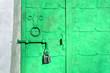 Leinwanddruck Bild - Closeup of iron bright green door with rivets, plates and worn metal door handle