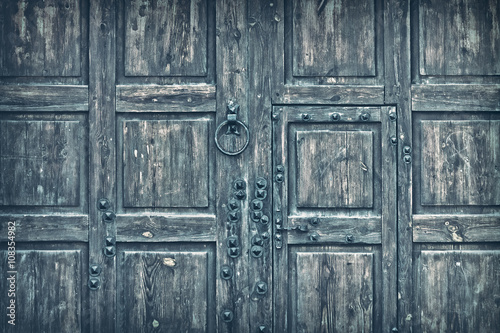 background old wooden gate toned gray with metal handle and rivets