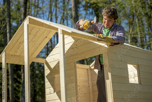 Fototapeta Young man using a mallet to fix a nail into a roof of a wooden p