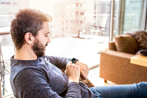 Fotografia  Man working from home using smart watch, living room
