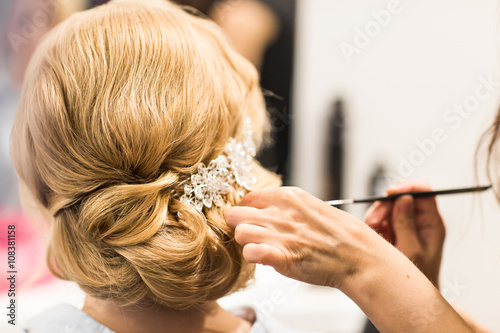 Hair stylist makes the bride before a wedding Fotobehang