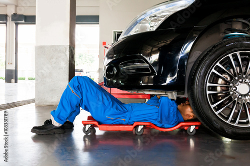 Mechanic in blue uniform lying down and working under car at auto service garage Fototapet