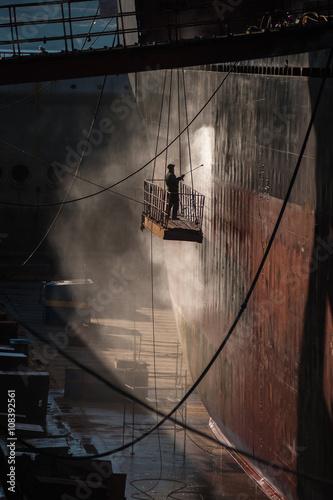 Fotografia Shipyard worker power washing a ship on dry dock.