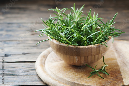 Foto Fresh green aromatic rosemary on the wooden table