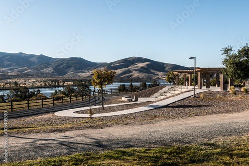 Fotografie, Obraz  Early morning light on amphitheater with Lower Otay Lake and mountain range in the background at Mountain Hawk Park in Chula Vista, California