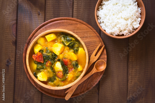 Deurstickers Klaar gerecht Pumpkin, mangold, potato and tomato curry dish in wooden bowl with rice, photographed with natural light