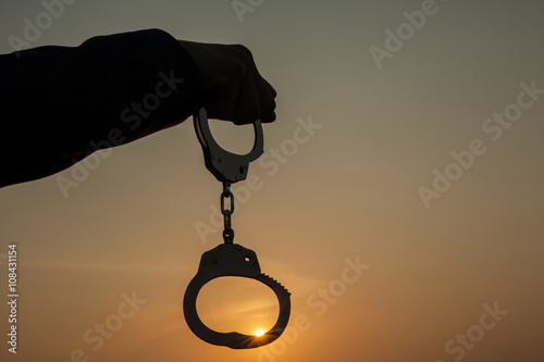 Business Man holding handcuffs after releasing over sunset background Wallpaper Mural