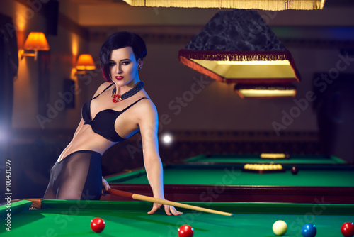 Fotografie, Tablou  Hot sexy young woman at billiards club playing snooker