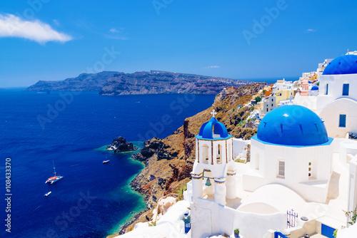 Fototapeta White architecture and churches with blue domes, Oia, Santorini, Greece obraz