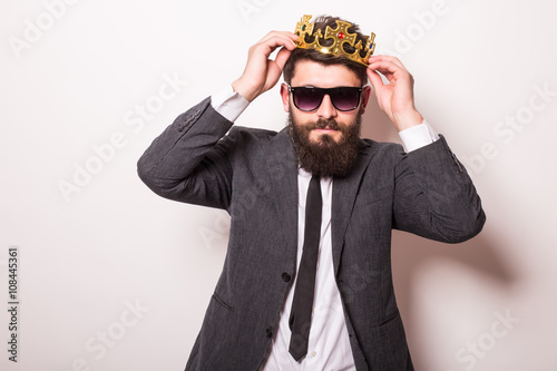 Fotografie, Obraz  Portrait handsome young cheerful man in suit with crown looking at camera with s