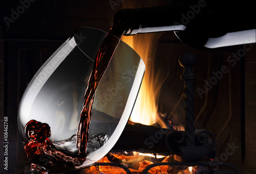 Photo  glass with red wine near the fireplace