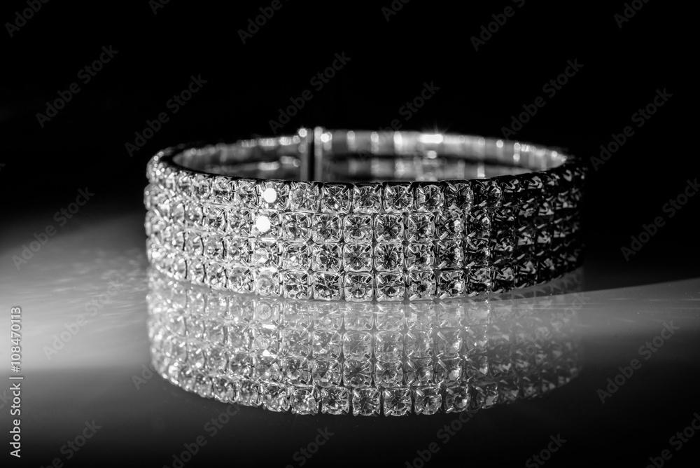 Valokuva  bracelet made of zirconium on a shiny glass surface