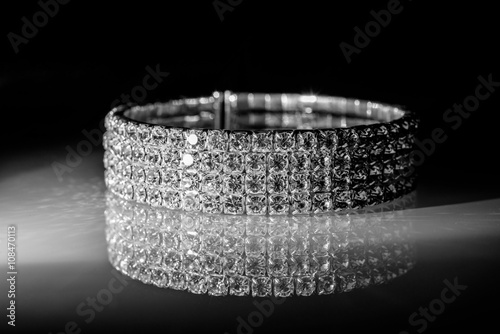 Fényképezés bracelet made of zirconium on a shiny glass surface