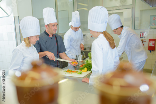 Chef teaching students on cookery course Wallpaper Mural