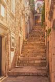 Fototapeta Uliczki - Narrow street and stairs in the Old Town in Dubrovnik, Croatia, Mediterranean ambient, warm filter, lens flare