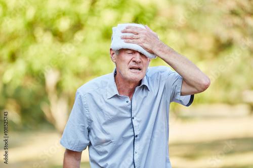 Fotografie, Obraz  Alter Mann kühlt Kopf mit feuchtem Tuch