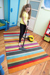 girl cleaning floor with hoover , The girl is vacuuming the carpet