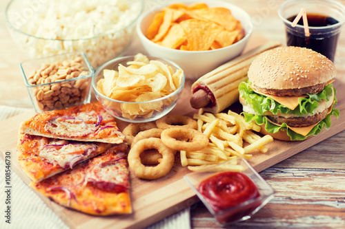 Fototapeta close up of fast food snacks and drink on table obraz