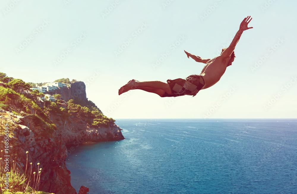 Fototapeta Mann springt von Klippe ins Meer