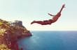 canvas print picture - Mann springt von Klippe ins Meer