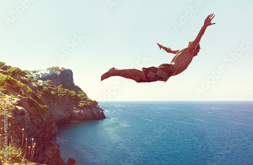 Fotografie, Obraz Mann springt von Klippe ins Meer